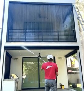 a Shine employee cleaning a window screen